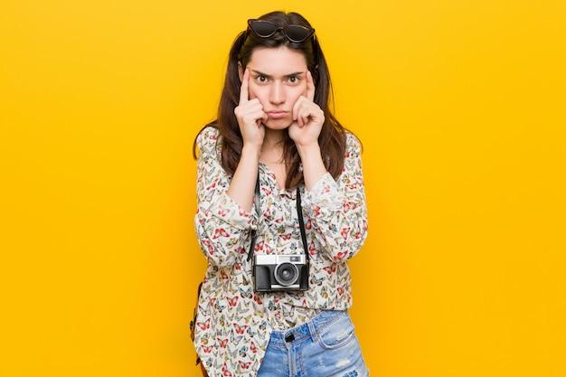 Молодая брюнетка путешественник женщина сосредоточена на задаче, сохраняя указательные пальцы, указывая головой. Premium Фотографии