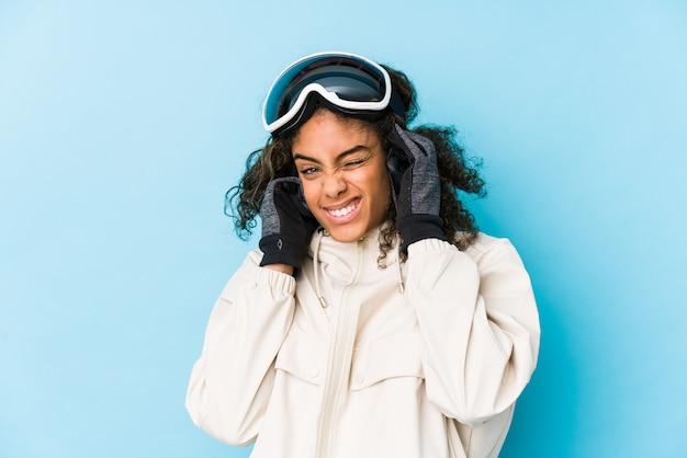 Молодая афро-американская женщина лыжника изолировала покрывать уши руками. Premium Фотографии