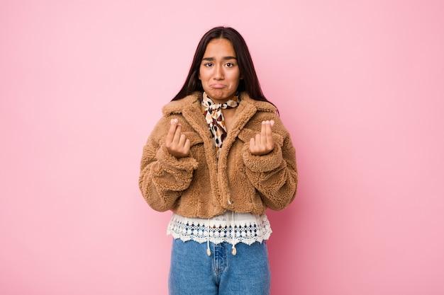 彼女はお金がないことを示す短い羊皮のコートを着ている若い混血のインドの女性。 Premium写真