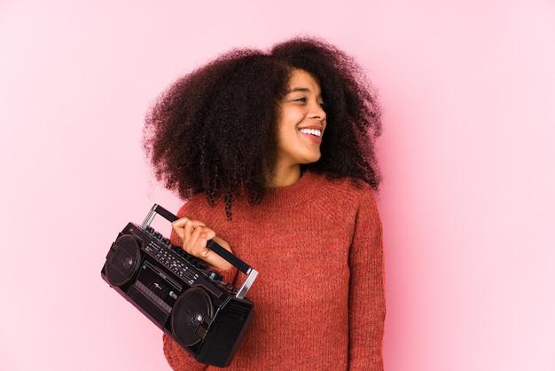分離されたカセットを保持している若いアフロ女性は笑みを浮かべて、陽気で快適な脇に見えます。 Premium写真