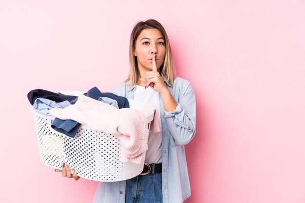 Молодая женщина кавказской, собирание грязную одежду, сохраняя в тайне или прося молчания. Premium Фотографии