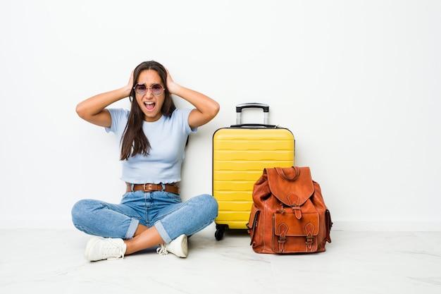 あまりにも大きな音を聞かないようにしようと手で耳を覆って旅行に行く準備ができている若い混血インドの女性。 Premium写真