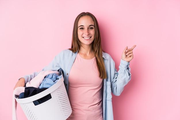 笑顔と脇を指して、空白で何かを見せて汚れた服を拾う若い女性 Premium写真