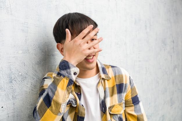 恥ずかしいと同時に笑っている若い中国人男性の顔のクローズアップ Premium写真