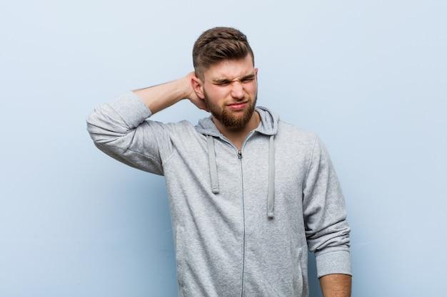座りがちなライフスタイルのため首の痛みに苦しんでいる若いハンサムなフィットネス男。 Premium写真