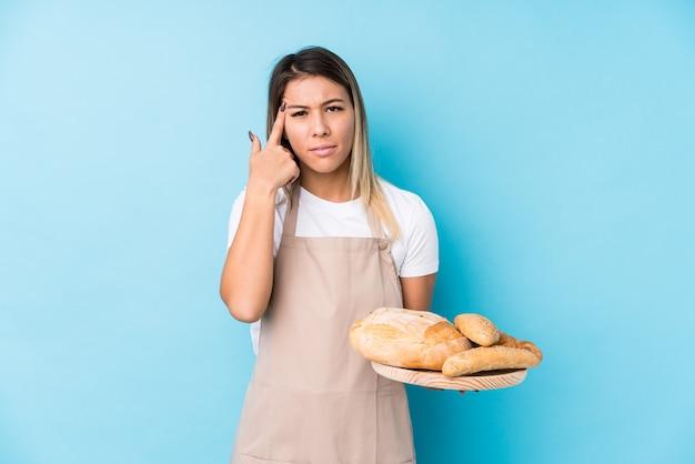Молодая кавказская женщина хлебопека изолировала показывать жест разочарования с указательным пальцем. Premium Фотографии