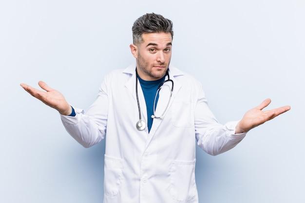 Молодой красивый доктор человек сомневаясь и пожав плечами в допросе жест. Premium Фотографии