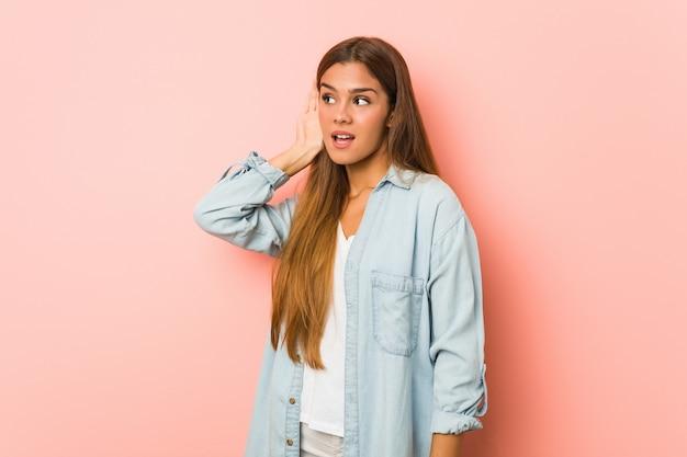 Молодая стройная женщина пытается слушать сплетни. Premium Фотографии