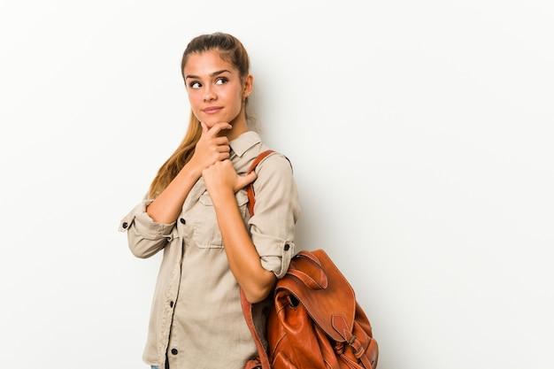 若い白人女性は疑わしいと懐疑的な表情で横に見て旅行の準備ができています。 Premium写真