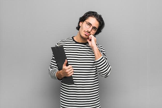 コピースペースを見て、悲しいと物思いにふける感じの目録を保持している若い従業員の男。 Premium写真