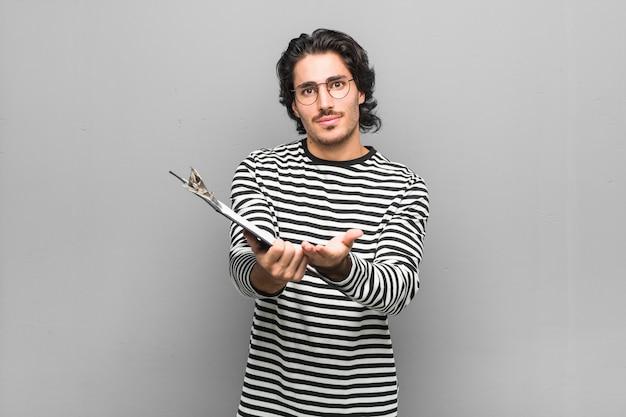 カメラに提供している手のひらで何かを保持している在庫を保持している若い従業員の男。 Premium写真