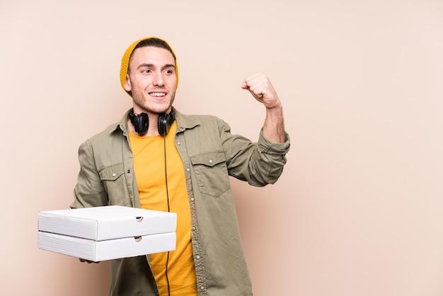 勝利の後に拳を上げるピザを保持している若い白人男 Premium写真