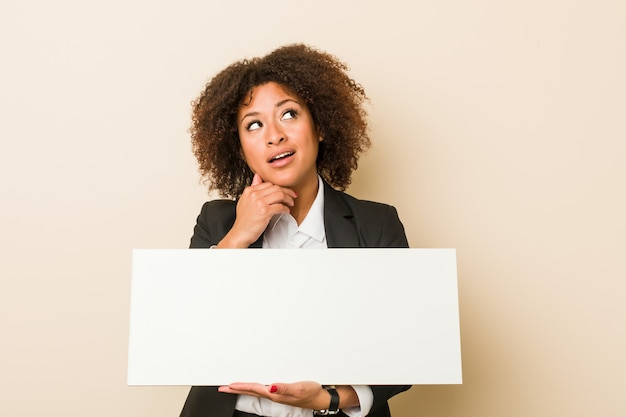 Молодая афро-американская женщина проводя плакат смотря косой с сомнительным и скептическим выражением. Premium Фотографии