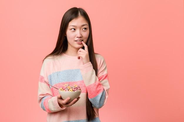 シリアルボウルを持つ若いアジア女性は、コピースペースを見て何かについて考えてリラックスしました。 Premium写真