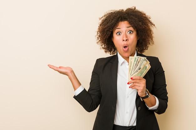 Молодая женщина афроамериканца держа доллары впечатлила держащ космос экземпляра на ладони. Premium Фотографии