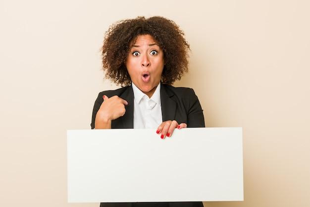 Молодой афроамериканец женщина, держащая плакат удивлен, указывая на себя, широко улыбаясь. Premium Фотографии