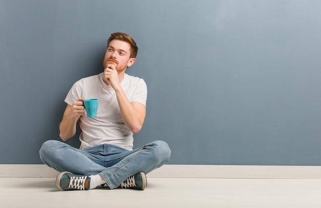 疑って混乱して床に座って若い赤毛学生男。彼はコーヒーマグを持っています。 Premium写真