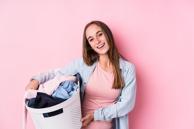 汚れた服を拾う若い白人女性は笑って、楽しんで分離しました。 Premium写真