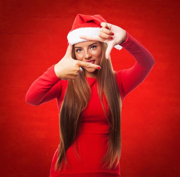 赤い背景に彼女の指を使ってフレームを作る女 無料写真