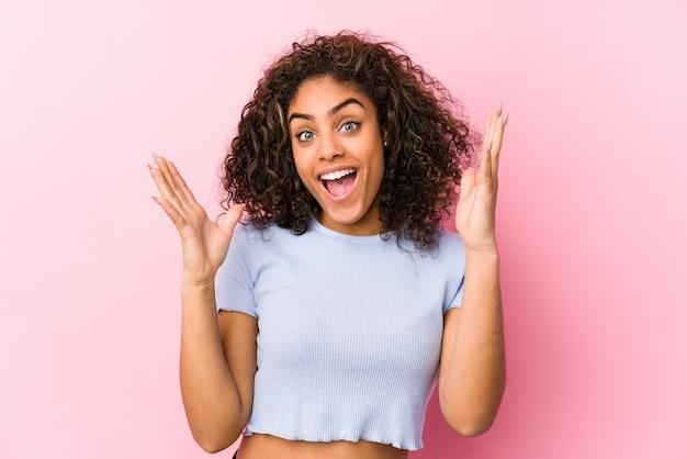 ピンクの背景の若いアフリカ系アメリカ人女性は、嬉しい驚きを受け取って、興奮し、手を上げます。 Premium写真
