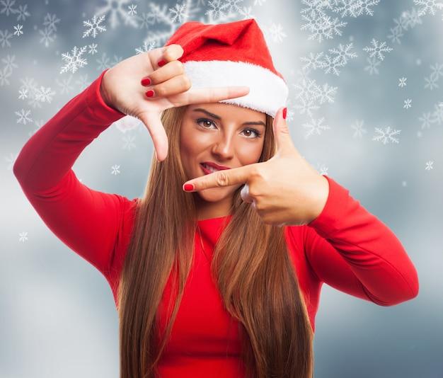 雪の背景に彼女の指を使ってフレームを作る女 無料写真