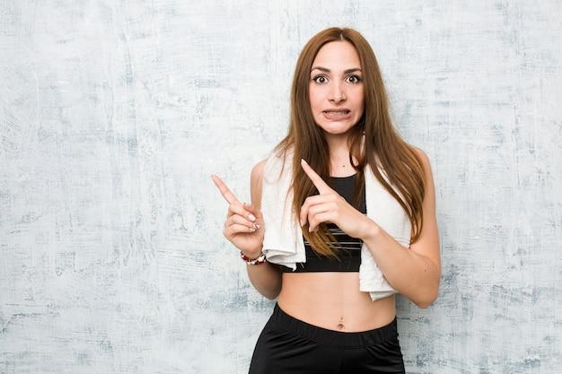 Молодая женщина фитнес шокирован, указывая с указательными пальцами на копией пространства. Premium Фотографии