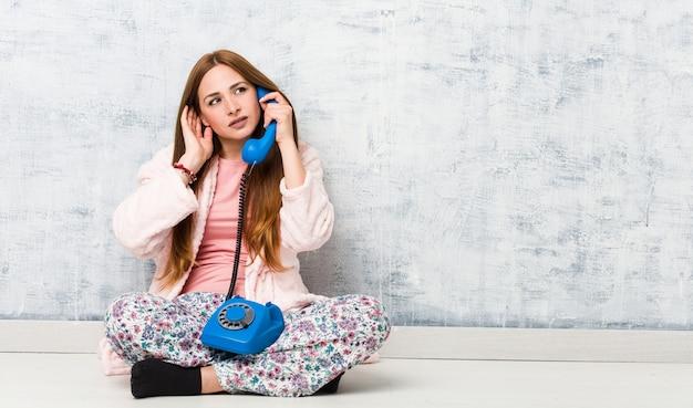 Молодая кавказская женщина держа наземную линию связи пробуя слушать сплетню. Premium Фотографии