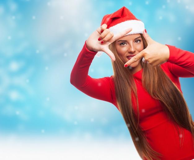 雪が降っている間女性は彼女の指でフレームを作ります 無料写真