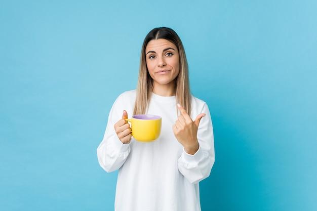 Молодая кавказская женщина держа кофейную чашку указывая с пальцем на вас как будто приглашая приблизиться. Premium Фотографии