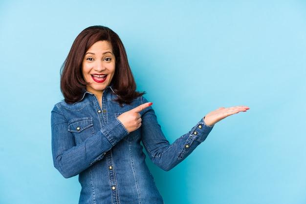 青い中年女性が手のひらにコピースペースを保持して興奮しています。 Premium写真