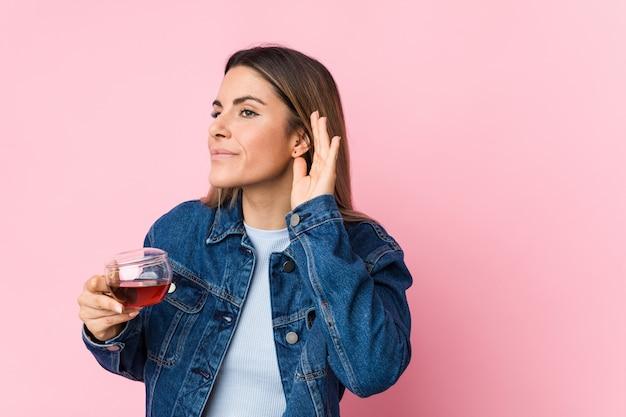 Молодая кавказская женщина держа чашку чая пробуя слушать сплетню. Premium Фотографии