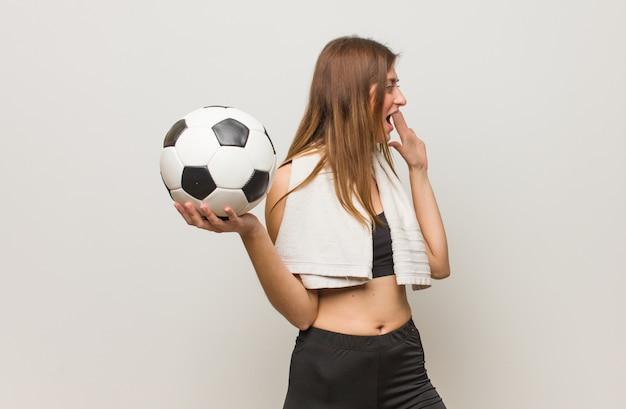 Молодые фитнес русской женщины шепот сплетни подтекст. проведение футбольного мяча. Premium Фотографии