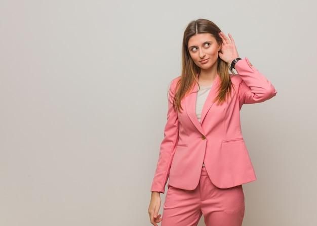 Молодая деловая русская девушка пытается слушать сплетни Premium Фотографии