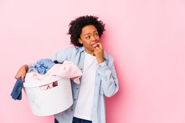 洗濯をしている中年のアフリカ系アメリカ人女性は、コピースペースを見て何かについてリラックスした思考を分離しました。 Premium写真