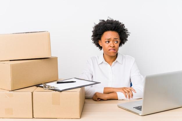 倉庫管理者は、ラップトップで配達を確認し、混乱し、疑念を抱き、不安を感じています。 Premium写真