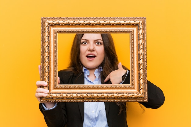 Молодой пышные плюс размер бизнес женщина, держащая кадр удивлен, указывая на себя, широко улыбаясь. Premium Фотографии