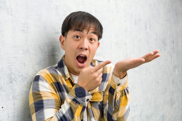 手で何かを保持している若い中国人の顔のクローズアップ Premium写真