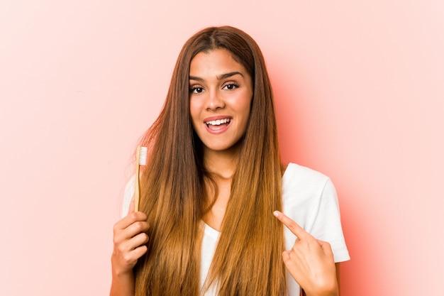 歯ブラシを保持している若い白人女性は、自分自身を指して驚いて、広く笑っています。 Premium写真
