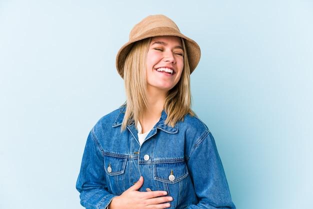 Молодая блондинка кавказских изолированных смех счастливо и весело держать руки на животе. Premium Фотографии