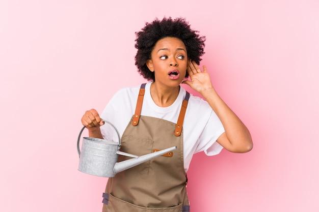 Молодая афро-американская женщина садовника пробуя слушать сплетню. Premium Фотографии