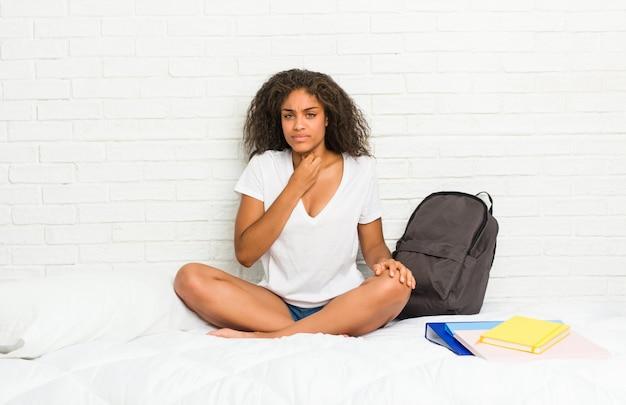 ベッドの上の若いアフリカ系アメリカ人学生の女性は、ウイルスや感染症のため喉の痛みに苦しんでいます。 Premium写真