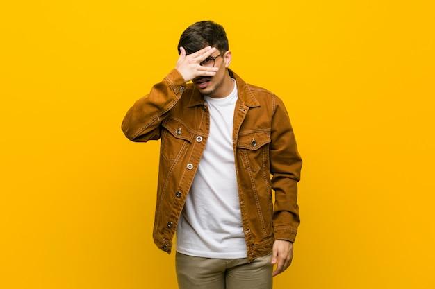 ヒスパニック系のカジュアルな若者が、顔を覆う恥ずかしい指の間で点滅します。 Premium写真