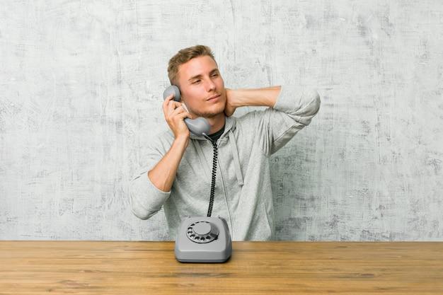 頭の後ろに触れる、考えて、選択をするヴィンテージの電話で話している若い男。 Premium写真