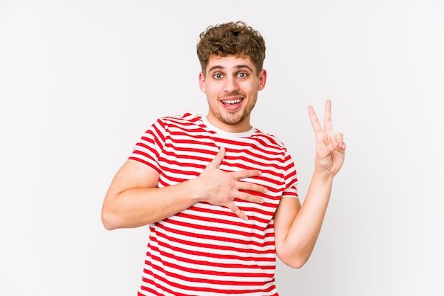 若いブロンドの巻き毛の白人男性は、誓いを取って、胸に手を置いて分離しました。 Premium写真