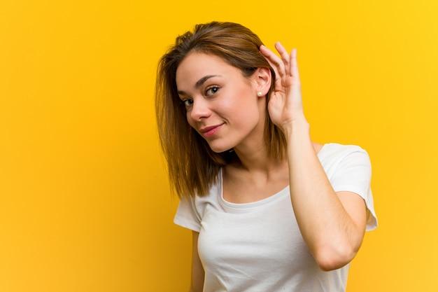 Молодая естественная кавказская женщина пробуя слушать сплетню. Premium Фотографии