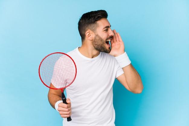 Молодой красавец, играя в бадминтон изолированные кричать и держа ладонь возле раскрытой пасти. Premium Фотографии