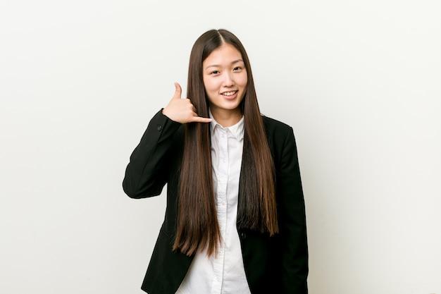 指で携帯電話のジェスチャーを示す若いかなり中国ビジネス女性。 Premium写真