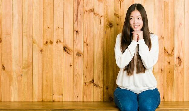 Молодая китайская женщина сидя на деревянном месте держит руки под подбородком, смотрит счастливо в сторону. Premium Фотографии