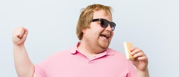 アイスクリームを保持している白人のクレイジーブロンドデブ男 Premium写真