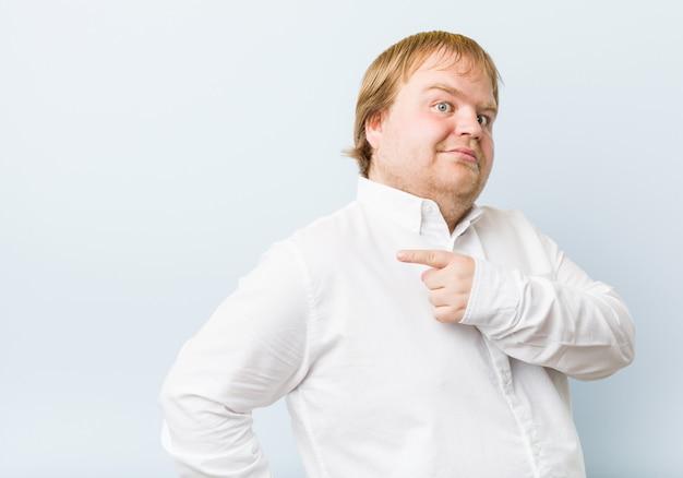 笑顔で脇を指して、空白で何かを示す若い本物の赤毛のデブ男。 Premium写真